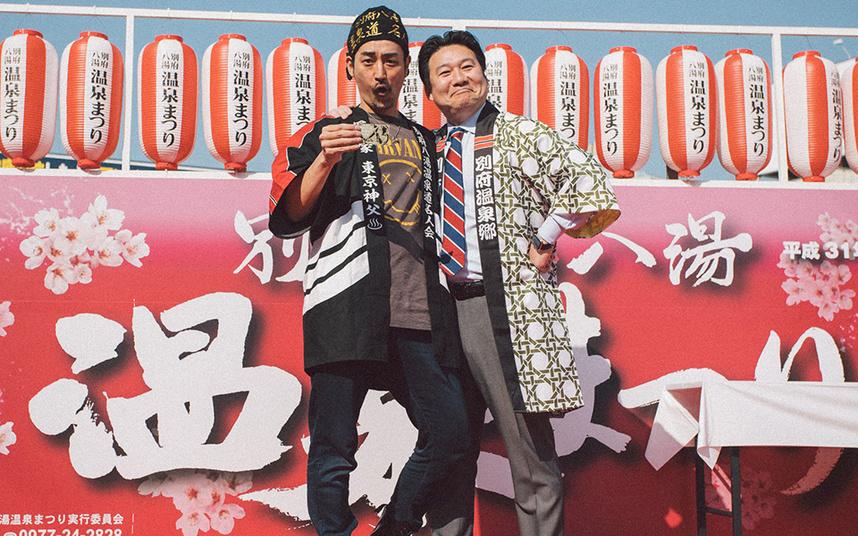 2019年の別府八湯温泉まつりにて。 左が東京神父。右は別府市長。